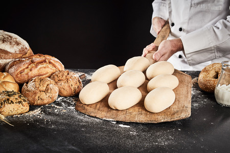 Ready formed dough for loaves of bread on a wooden paddle held by a baker as he prepares to place them in the oven for baking Imagens