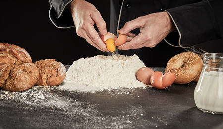 Baker breaking eggs into a heap of baking flour with milk in a jug as he prepares his speciality bread
