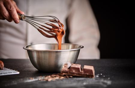Küchenchef, der geschmolzene Schokolade in einer Rührschüssel aus Edelstahl mit einem alten Vintage-Schneebesen in Nahaufnahme auf seiner Hand verquirlt