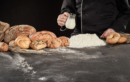 Specialist baker pouring milk into a heap of flour as he prepares the dough for his gourmet bread displayed alongside