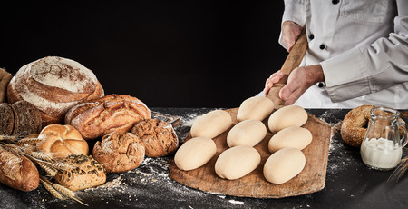 Raw dough for loaves of bread on a wooden paddle ready to be placed in the oven for baking held in the hands of a chef or baker Archivio Fotografico - 118075662