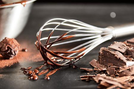Dripping melted chocolate on an old vintage whisk alongside a round bonbon or cookie and chopped bar of chocolate