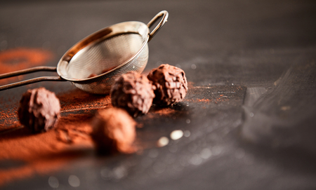 Chocolate bonbons sprinkled with cocoa powder on a kitchen counter alongside a metal sieve and copy space