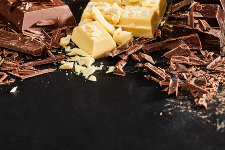 Shavings and pieces of white and milk chocolate, viewed in close-up from high angle on dark table surface background with copy space. Cooking ingredients concept