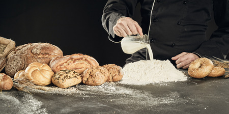 Panorama banner of a baker pouring milk onto a heap of baking flour to make dough with a large display of speciality read alongside him