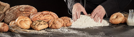 Baker preparing a mound of flour for ingredients to be added while making speciality bread many of which are displayed alongside, panorama banner Imagens
