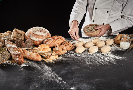Baker sprinkling seeds or crushed wheat onto dough ready formed into rolls on a floured kitchen counter with assorted speciality bread alongside Banco de Imagens - 118075680