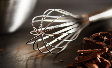 Chopped chocolate for baking alongside an old fashioned metal whisk on a wooden kitchen table in close up Stock Photo - 118075681