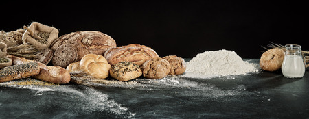 Panorama display of gourmet breads with dough, milk and flour ingredients over a floured kitchen table with copy space