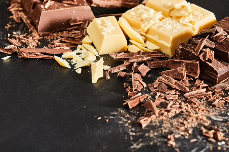 Chocolate for cooking ingredients concept with pieces and shavings of milk and white chocolate, viewed from high angle in close-up on dark surface background with copy space