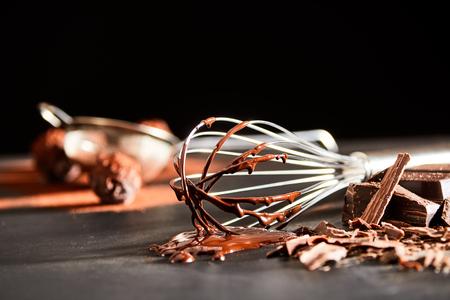Zubereitung von Schokoladenbonbons mit einem alten Schneebesen, um die geschmolzene Schokoladenzutat zu schlagen, die auf einem Küchentisch in einem niedrigen Winkel liegt