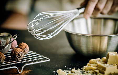 Hand of a chef holding an old metal whisk over a stainless steel mixing bowl with chocolate bonbons alongside Stock Photo