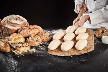 Ready to cook loaves of bread dough on a wooden paddle held by a chef over a counter with display of assorted gourmet breads Stock Photo