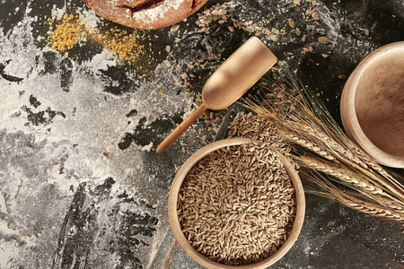 Still life of ears of fresh wheat, rustic bowl of seeds and flour scattered on a kitchen table viewed top down with copy space