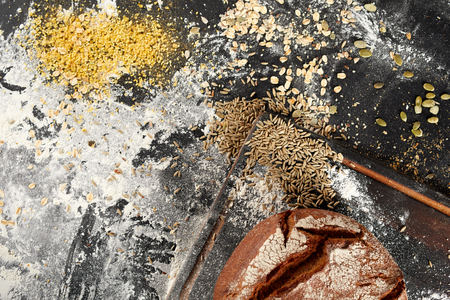 Assorted grain seeds with a freshly baked crusty loaf of bread and flour on a messy kitchen counter viewed from above