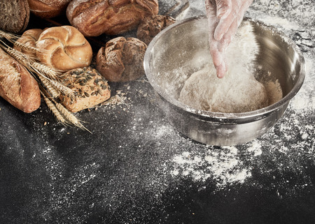 Baker dusting his dough with flour from his hands as he prepares the mixture in a bowl while making an assortment of breads on display