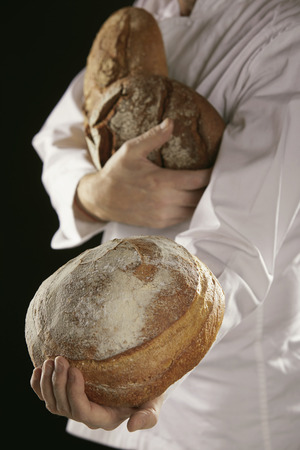 Baker in white uniform carrying fresh rye bread loaves in his hands Imagens