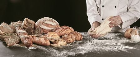Chef or baker kneading dough while making specialty bread on a black counter with a display of a variety of his products alongside