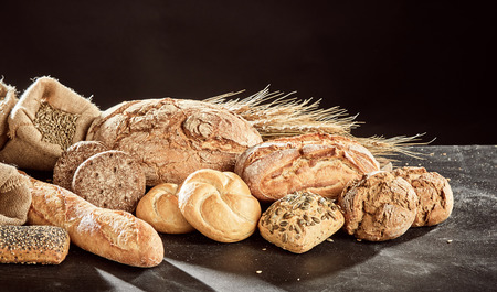 Fresh bread loaves assortment piled on dark table surface with grains of rye and wheat, against black
