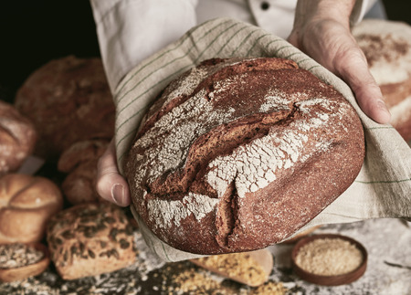 Baker holding freshly baked hot loaf of rye bread on towel in close-up, over the table with bread loaves and buns assortment