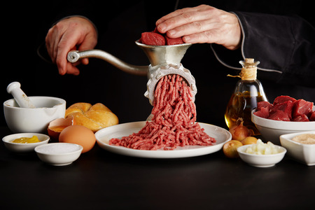 Man mincing beef with manual grinder on black kitchen table, viewed in close-up among bowls with cooking ingredients