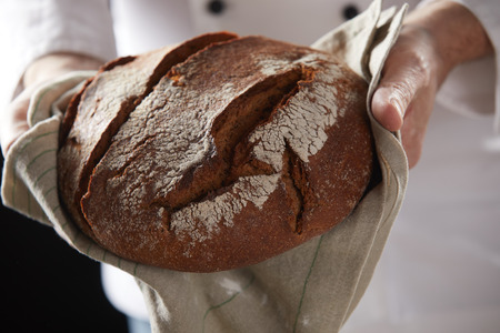 Professional baker holding hot fresh loaf of just baked rye bread on towel in close-up