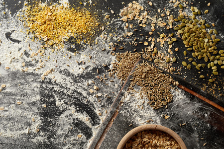 Bakery counter with flour and assorted whole grain seeds in scattered heaps ready to use as toppings on speciality bread viewed from overhead