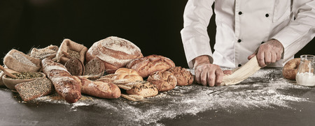 Baker kneading raw dough while making assorted speciality bread displayed alongside on a floured counter in panorama banner format Stockfoto