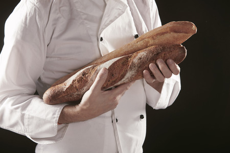 Baker in white uniform holding or carrying two baguettes of freshly baked rye bread, viewed in close-up against black Imagens