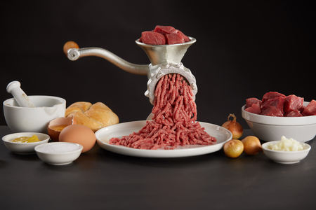 Meat grinder with pork or beef on kitchen with cooking ingredients in white bowls against black Stock Photo