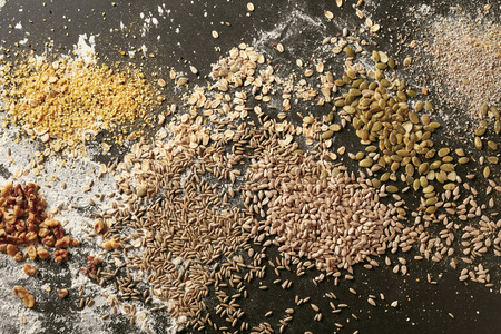 Assortment of whole grain and sunflower seeds for baking bread scattered on a bakery table with flour viewed full frame from above Imagens