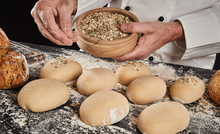 Baker sprinkling buns of raw bread with seeds placing spices with his fingers during preparation