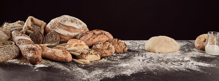 Rustic bread preparation concept with pile of freshly baked buns and loaves and raw dough on floured table surface.
