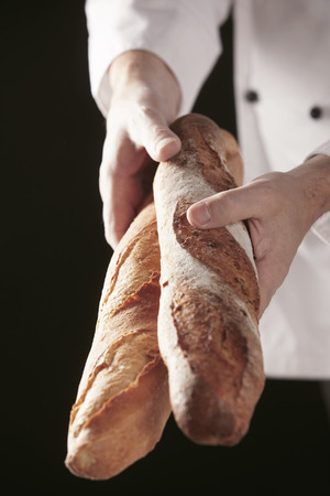 Hands of chef baker in white uniform, holding two long loaves of fresh baked bread in professional bakery or restaurant Imagens