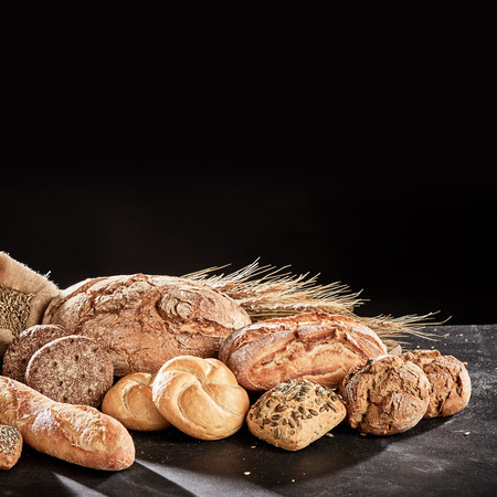 Pile of freshly baked rustic bread loaves and buns assortment on dark table surface against black Imagens
