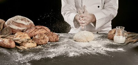 Chef flouring his dough with his hands as he prepares assorted speciality or regional bread on a flour covered table in panorama banner format Banco de Imagens
