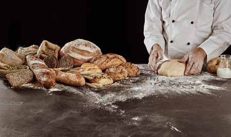 Bread preparation concept with pile of freshly baked crunchy rustic loaves and male baker in white uniform forming raw dough on floured table surface