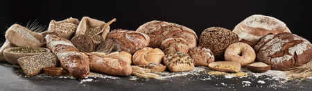 Panoramic banner with rustic bread assortment, decorated with seeds, cereal and flour, sitting on dark surface against white