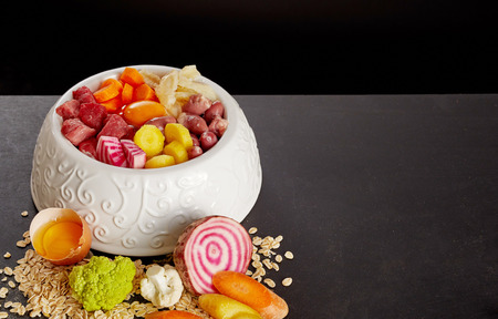 Bowl of healthy food mix of beef hearts, stomach and vegetables for dog or cat meal.