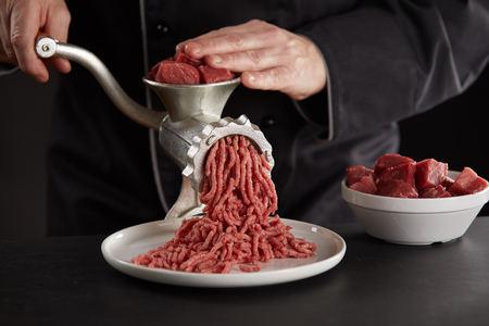 Uomo in uniforme nera che produce carne macinata di manzo o maiale con un vecchio macinino manuale in metallo. Pezzi di carne rossa fresca per tritare in ciotola bianca. Processo di preparazione della carne per le polpette, visto in primo piano