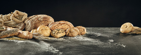Table with pile of bread assortment. Loaves of white and grey bread, buns and rustic sackcloth bug with cereal, sitting on floured surface against black