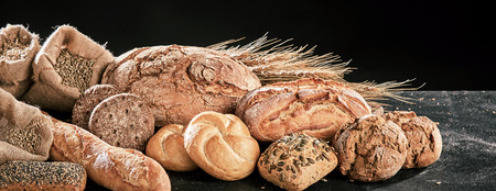 Freshly baked bread loaves assortment, with grains of cereals of wheat and rye on dark table surface.