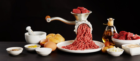 Red raw meat minced through old grinder, eggs, oil and other cooking ingredients on black Standard-Bild - 118972227