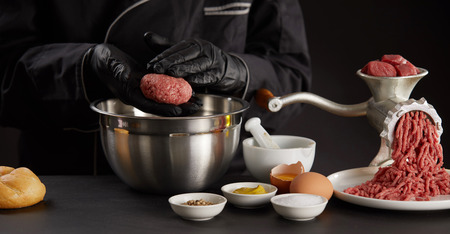 Cook in black gloves making meat balls of minced meat over metal bowl.