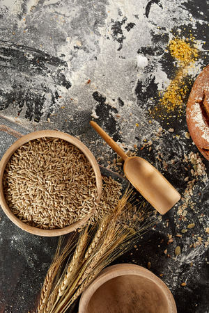 Still life with ears of golden wheat, seeds and flour in rustic wooden bowl on a messy kitchen table with copy space viewed from above