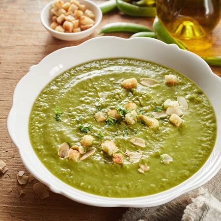 Bol gastronomique de soupe aux pois frais liquéfiée savoureuse et épaisse avec croûtons et amandes effilées vue en gros plan en grand angle pour un menu au format carré