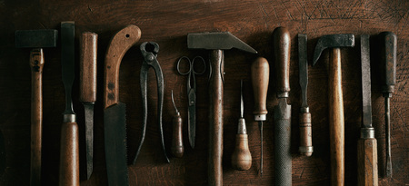 Panorama banner with row of wooden handled vintage hand tools for woodworking and carpentry in a flat life still lay