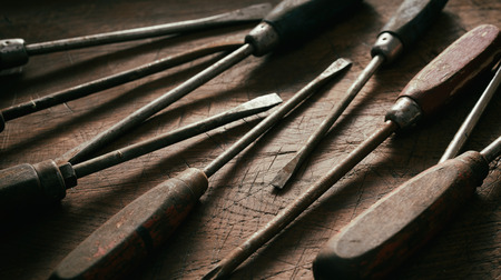 Close up on old worn vintage screwdrivers with rusting metal and worn wood handles in a panorama banner