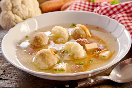 Specialist spring soup with German bone marrow dumplings in a broth with cauliflower carrots, fresh herbs and cheese