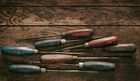 Selection of old wooden handled vintage screwdrivers arranged as a bottom border on old rustic wood with copy space and vignette Фото со стока